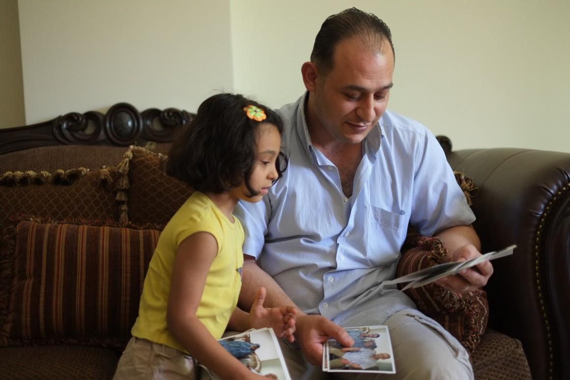 أدهم الهبيل وابنته إيناس في بيتهم، رام الله. تصوير: أليكس ليـﭭـاك