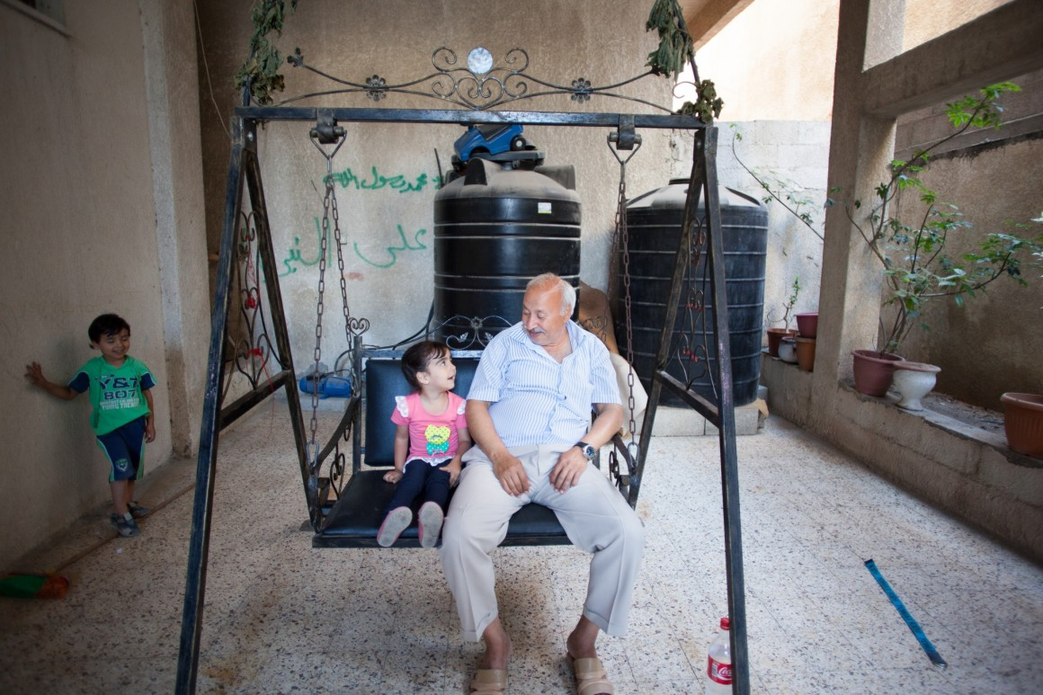 Abed Abu-Sido and two of his grandchildren at his home in Gaza. Photo: Eman Mohammed